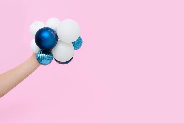 女性の手はピンクの背景に白と青のクリスマスツリーのボールを保持しています。コンセプト2021