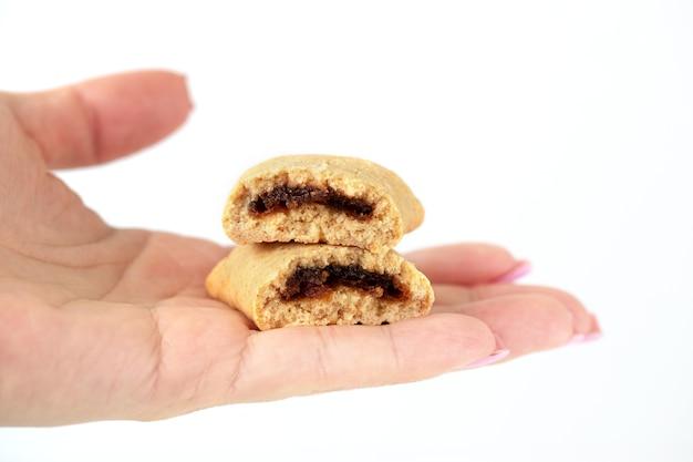 女性の手は、白い背景に果物がいっぱいの壊れたクッキーを差し出します