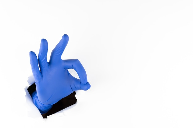 Рука женщины в синей резиновой перчатке показывает пальцами «ок» через рваную дырочку в белой бумаге. все будет отлично. копировать пространство