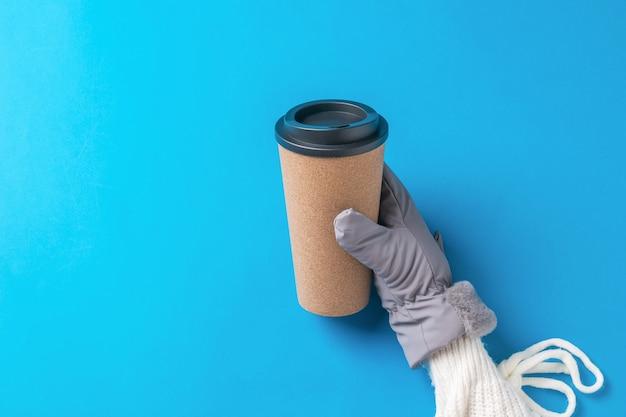Женская рука в перчатке с бумажным кофейным стаканом на синей поверхности. горячий напиток и варежки.