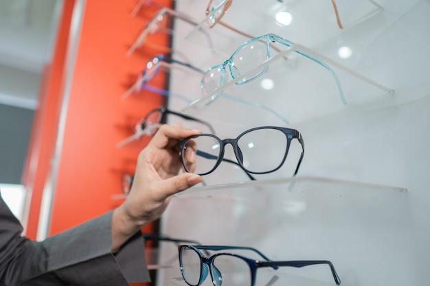 女性の手が眼科クリニックの窓に貼り付けられた眼鏡を持っています
