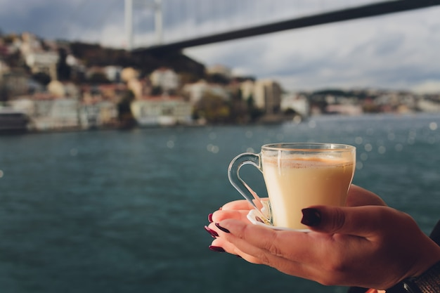 女性の手が、波打つ水と遠くのイスタンブールの霧の乙女の塔を背景に、トルコのサレップサーレップと呼ばれるシナモンが入った白いカップの熱い乳飲料を持っています。