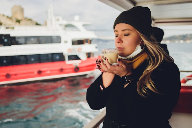여자의 손은 졸졸 흐르는 물과 거리, 이스탄불에서 안개가 자욱한 maiden s tower의 배경에 터키 salep sahlep이라는 계피와 함께 뜨거운 우유 음료의 흰색 컵을 들고 있습니다.