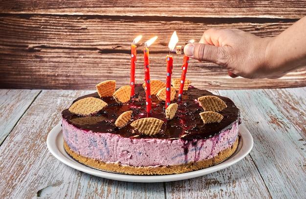 비스킷 조각으로 장식 된 숲 과일 무스 케이크에 여자의 손 조명 촛불