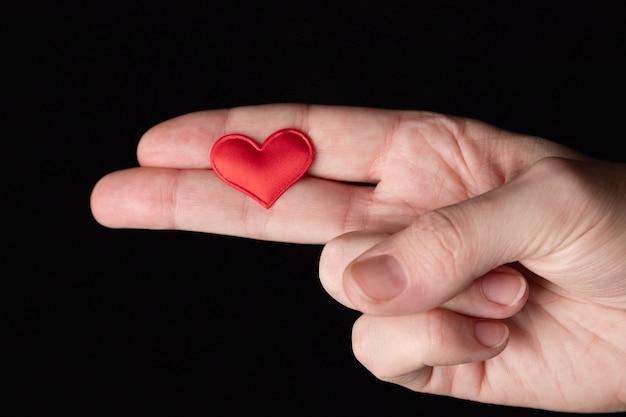 女性の手、手のひら、ジェスチャーは、彼女の指で銃を作り、その上に赤いハートがあります。