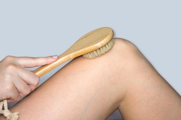여성의 손이 나무 브러시로 다리를 통과하고, 피부를 탄력 있게 하고 혈액 순환을 증가시키기 위해 건식 마사지를 합니다. 스파, 뷰티 트리트먼트