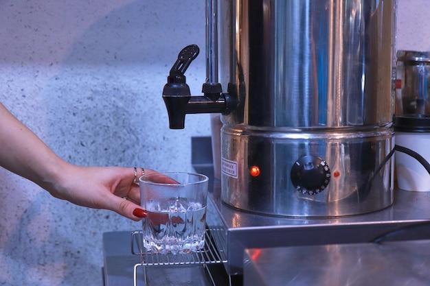 女性の手が蛇口を押して、ボイラーからテーブルの透明なガラスにお湯を注ぎます