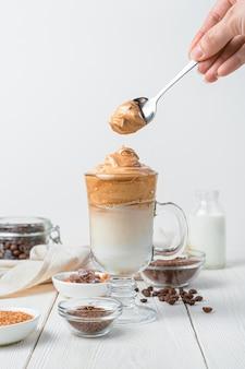 女性の手は、白い壁のダルゴナ コーヒーのグラスに泡を入れます。ミルクと氷で飲む韓国コーヒー。