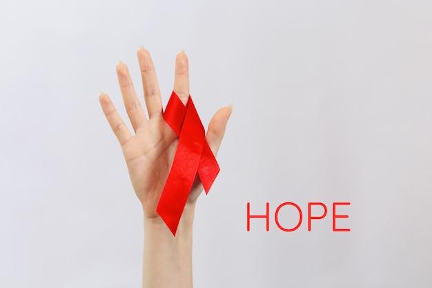 Поднимается женская рука с красной лентой на пальце. белый фон со словом надежда. концепция всемирного дня борьбы со спидом.