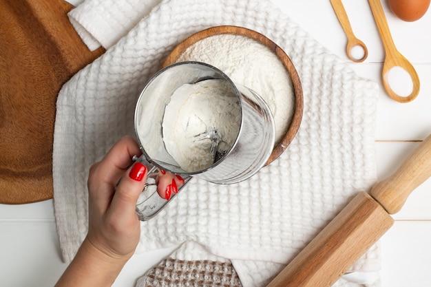 Женская рука просеивает муку специальной кружкой с ситом возле белого полотенца, деревянной скалкой и ложками. плоская планировка