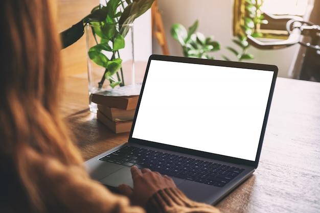 木製のテーブルに空白の白いデスクトップ画面でノートパソコンのタッチパッドを使用して触れる女性の手