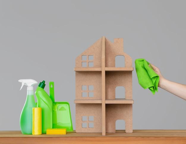 Женская рука моет символический дом зеленой тканью, рядом с домом - красочный набор инструментов для уборки.