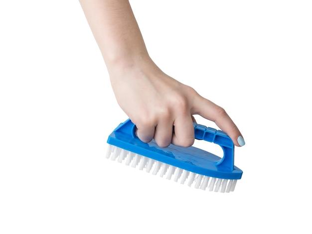 白い表面に分離された青いクリーニングブラシを持つ女性の手。家の掃除用のアイテム。