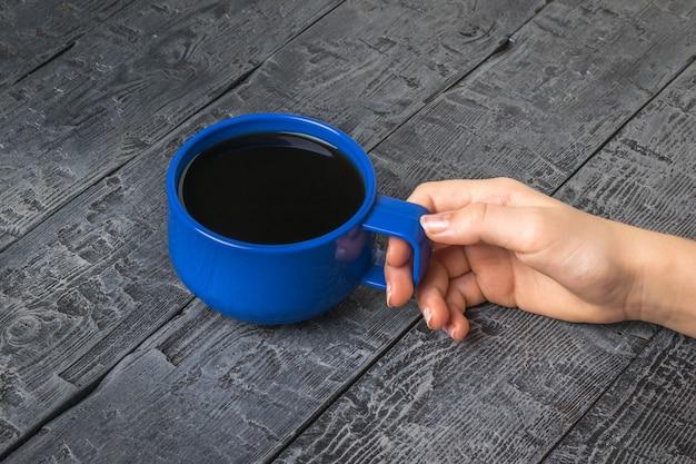 나무 테이블에 커피 한잔과 함께 여자의 손. 인기있는 상쾌한 음료를 들고있는 여성의 손.