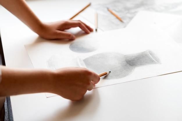 Женская рука с карандашом. рисует натюрморт. изобразительное искусство