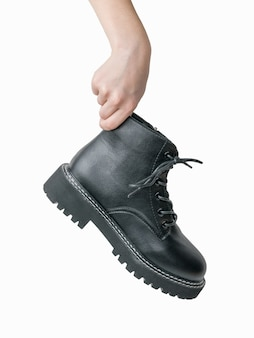 흰색에 고립 된 거친 가죽 부츠와 여자의 손. 캐주얼 신발.