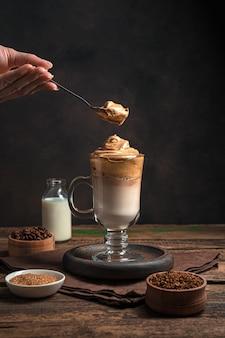 茶色の壁にスプーンとホイップ フォームとダルゴナ コーヒーのグラスを持つ女性の手。韓国の爽快ドリンク。サイドビュー、垂直ビュー。