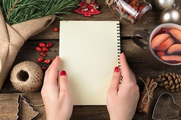 女性の手は、クリスマスの道具に囲まれたメモ帳を持っています。