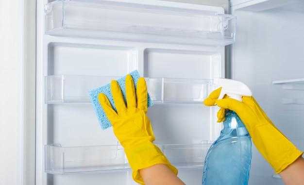 노란색 고무 보호 장갑과 파란색 스폰지에 여자의 손을 씻고 냉장고 선반을 청소합니다. 청소 서비스, 주부, 일상적인 가사. 창문 및 유리 표면 클리너 용 스프레이