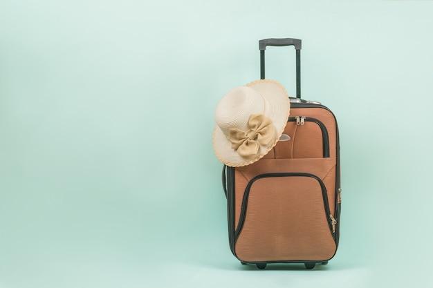 女性の帽子と青い背景にハンドルが付いた旅行スーツケース。テキスト用のスペース。夏の旅行のコンセプト。