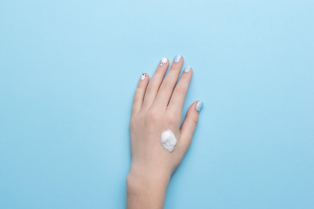 Левая рука женщины со стильным макияжем и каплей крема на синем. уход за кожей рук. плоская планировка.
