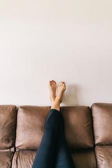 Ноги женщины высоко подняты на коричневом диване у себя дома