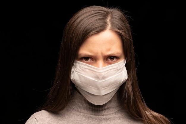 女性の緊張と落ち着きのない視線。白い医療マスクのクローズアップの子犬の肖像画。ウイルスの拡散と保護の危険。未来への恐怖