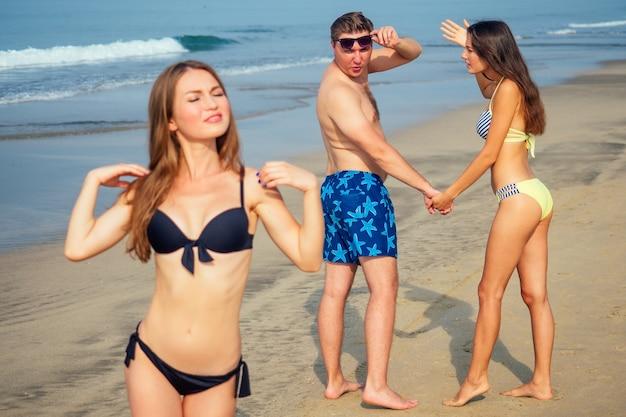 한 여자가 질투와 분노로 해변에서 다른 사람의 여자를보고 남자를 꾸짖습니다.