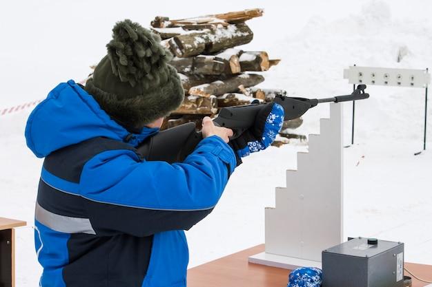 한 여성이 겨울에 열린 공간에서 목표물에 소총을 쏜다.