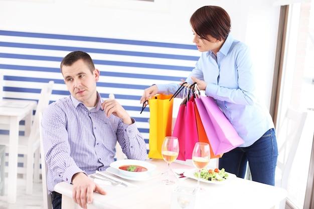 Женщина показывает свою новую покупку мужу в ресторане