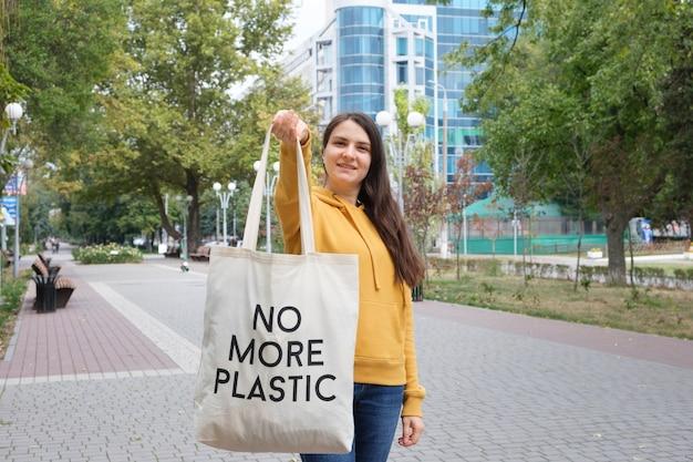 Женщина показывает тканевую многоразовую сумку, на которой написано, что больше нет пластика.