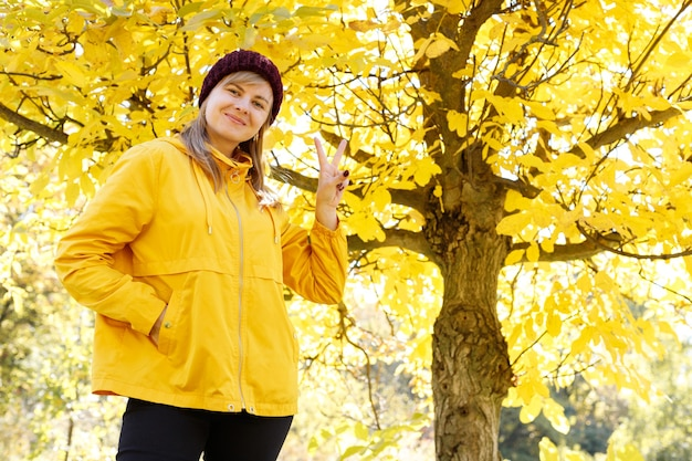 女性は黄色い紅葉を背景に平和の兆しを見せています。ポジティブ