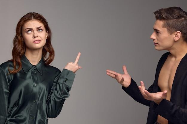 여자는 그녀의 엄지 손가락을 보여주고 의아해하는 남자는 회색 벽에 그의 손으로 제스처를 취합니다.