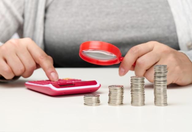 한 여성이 탁자에 앉아 계산기를 보며 다른 한편으로는 돋보기, 탁자 위의 동전 더미를 보고 있습니다. 비용 및 소득, 보조금, 세금 계산