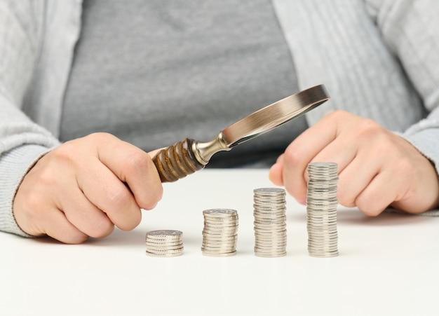 Женщина сидит за столом и держит деревянную лупу над стопками белых монет. понятие бюджетного планирования, экономии. поиск инвестиций