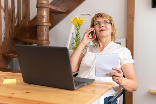 한 여성이 집에서 책상에 앉아 소셜 네트워크에서 노트북으로 작업합니다.