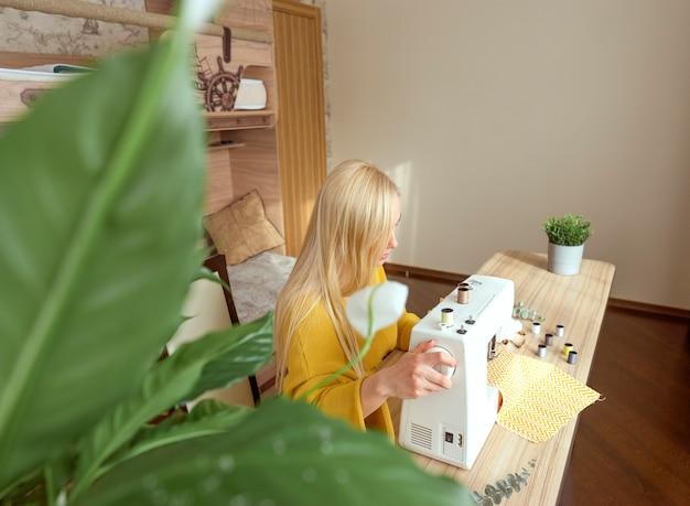Женщина сидит за швейной машинкой
