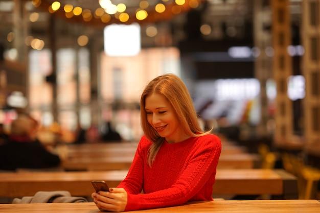 Женщина сидит в кафе и смотрит в свой телефон