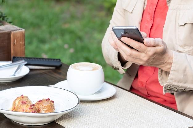 女性がコーヒーを飲みながら通りのカフェに座って、電話でメッセージを送信します。