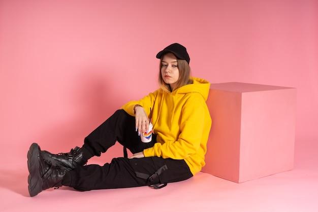 한 여성이 후드가 달린 운동복에 앉아 있고 종이컵 옆에 검은 색 모자를 쓰고 사랑은 사랑이란 단어와 무지개 lgbt가있는 하트
