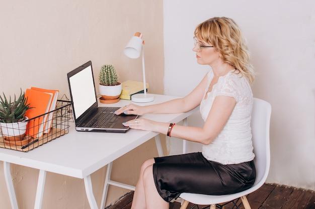 Женщина сидит в офисе и работает за ноутбуком копирайтер или менеджер удаленной работы