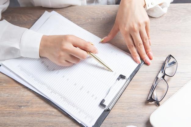 여자는 노트북 앞에 앉아 문서를 연구합니다. 광학 안경