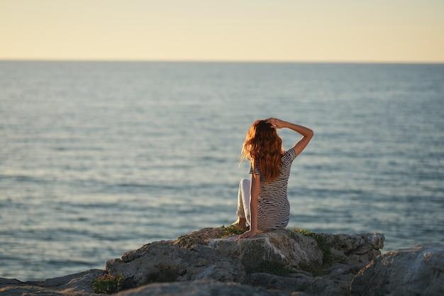 海の近くの大きな石の上に座って、山の夕日を眺める女性。高品質の写真