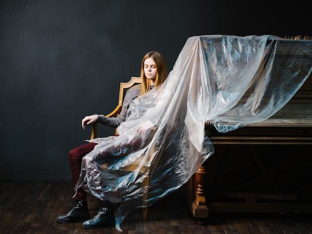 한 여자가 피아노 폴리에틸렌 어두운 배경 옆에 있는 의자에 앉아 있다