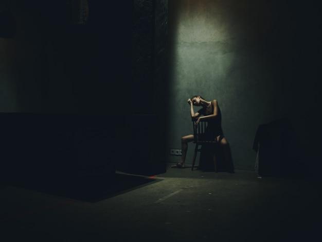 暗い部屋に足を広げ、上から光が降り注ぐ椅子に座っている女性