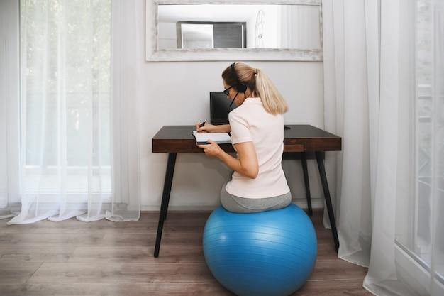 Женщина сидит на фитнес-мяче в наушниках и работает дома во время карантина