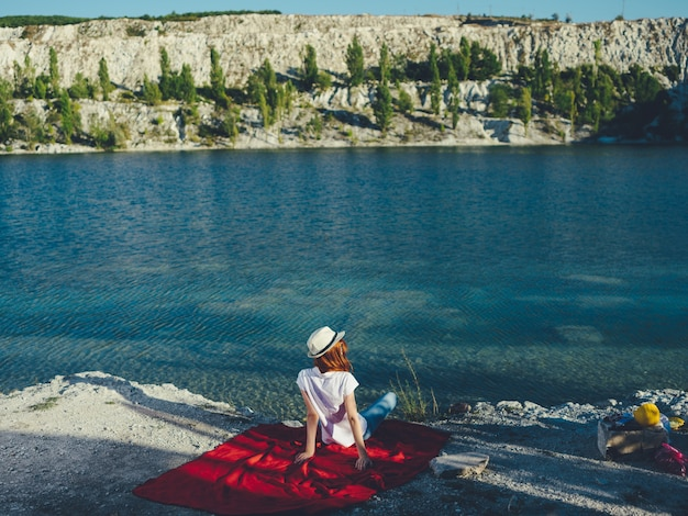 한 여자가 강 근처에있는 붉은 천 위에 앉아 있고 머리에는 모자를 쓰고 있습니다. 고품질 사진