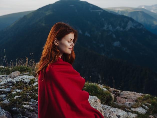 여자는 산에서 야외에서 빨간 담요로 덮여 돌에 앉아