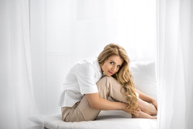 Женщина сидит на диване и гладит свои усталые опухшие ноги после долгого рабочего дня.
