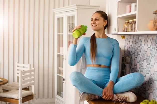 女性が台所のカウンターに座って、スポーツボトルから水を飲みます。健康的なライフスタイルのコンセプト。